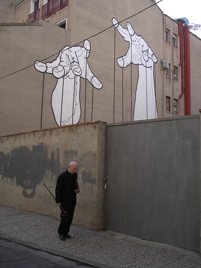 Luis Pita | Fotografía | Photography | Desconocidos | Unknown people | (2008) El que mueve los hilos | That which pulls the strings | viejo sacerdote caminando debajo de un gran mural que representa las manos de titiritero manejando los violines de un títere | old priest walking under a large mural depicting the hands of puppeteer pulling the puppet violins