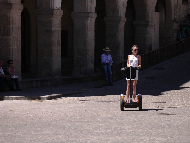 Luis Pita | Fotografía | Photography | Desconocidos | Unknown people | (2013) Mediodía en Trujillo | Noon at Trujillo | joven chica con pequeño vestido blanco cruza la plaza medieval de Trujillo en un segway | Young girl with little white dress crossing the medieval square of Trujillo on a segway