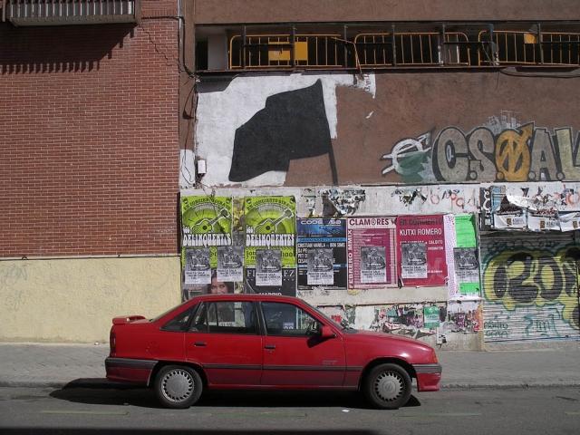 Luis Pita | Fotografía | Photography | Visiones exteriores | Exterior Visions |  (2009) Suburbia - Madrid | bandera negra, coche rojo viejo, carteles de rock | black flag, red old car, rock posters